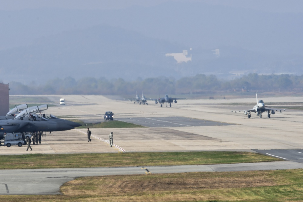A Royal Typhoon FGR4 taxis down the runway as Republic of Korea Air Force F-15K Slam Eagle crews perform shutdown procedures during Invincible Shield on Osan Air Base, Republic of Korea, Nov. 8, 2016. Invincible Shield is an exercise intended to bolster the strong partnership between the ROK, the United States and the United Kingdom while improving combat capability in the Pacific region. (U.S. Air Force photo by Tech. Sgt. Rasheen Douglas)