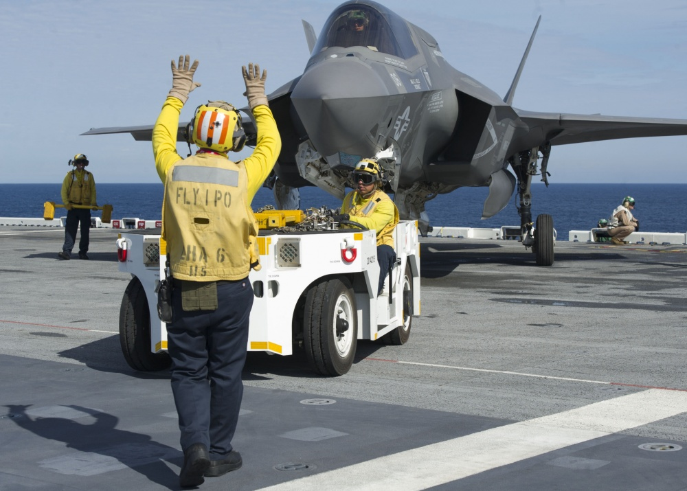 An F-35B Lightning II aircraft is taxied on the flight deck of amphibious assault ship USS America  (U.S. Navy photo by Petty Officer 1st Class Benjamin Wooddy/Released)
